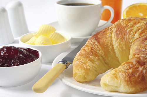 Continental breakfast with croissants, strawberry jam, butter curls, coffee and orange juice.